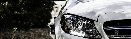 The headlight and front of a luxury, executive, business car