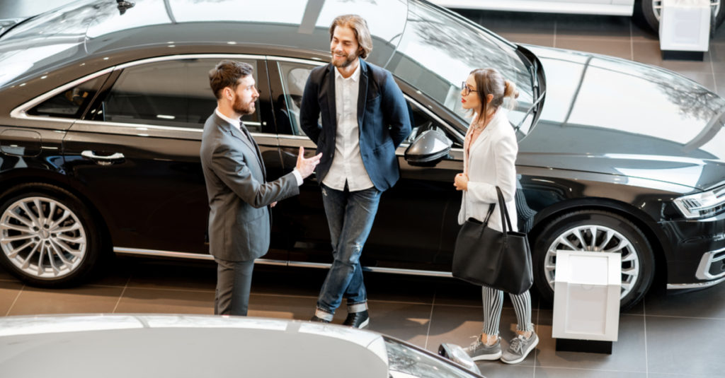 young-couple-with-salesman-in-car-showroom